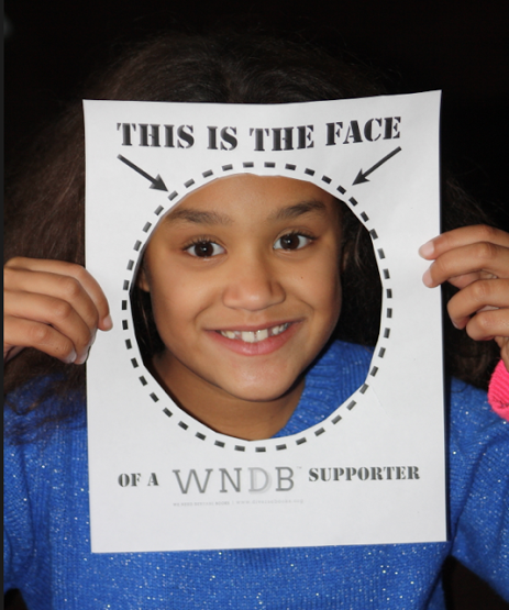 A young WNDB supporter uses one of our #SupportWNDB cue cards.