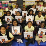 A group of students with their new picture books after a WNDB in the Classroom event.